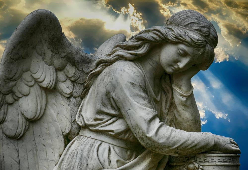 Статуя ангела - олицетворение святости - на фоне света, пробивающегося сквозь тучи