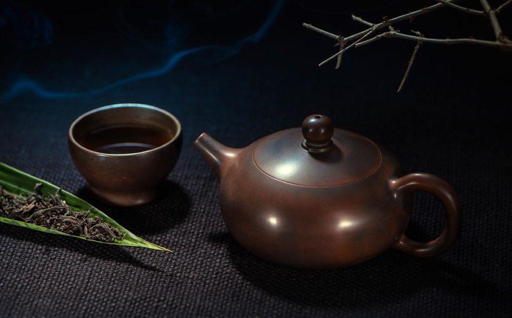 Коричневый чайник рядом с кружкой чая