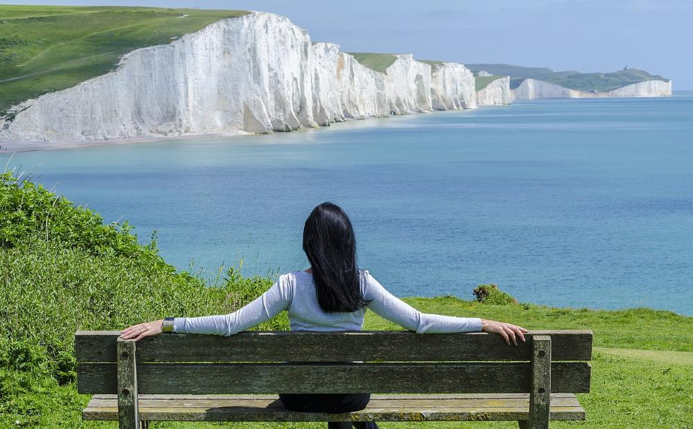 Девушка, расслабленно сидящая на скамейке перед морем