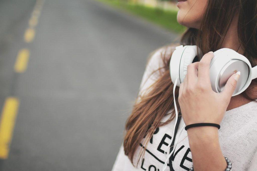 Девушка касается рукой наушников, спущенных на шею