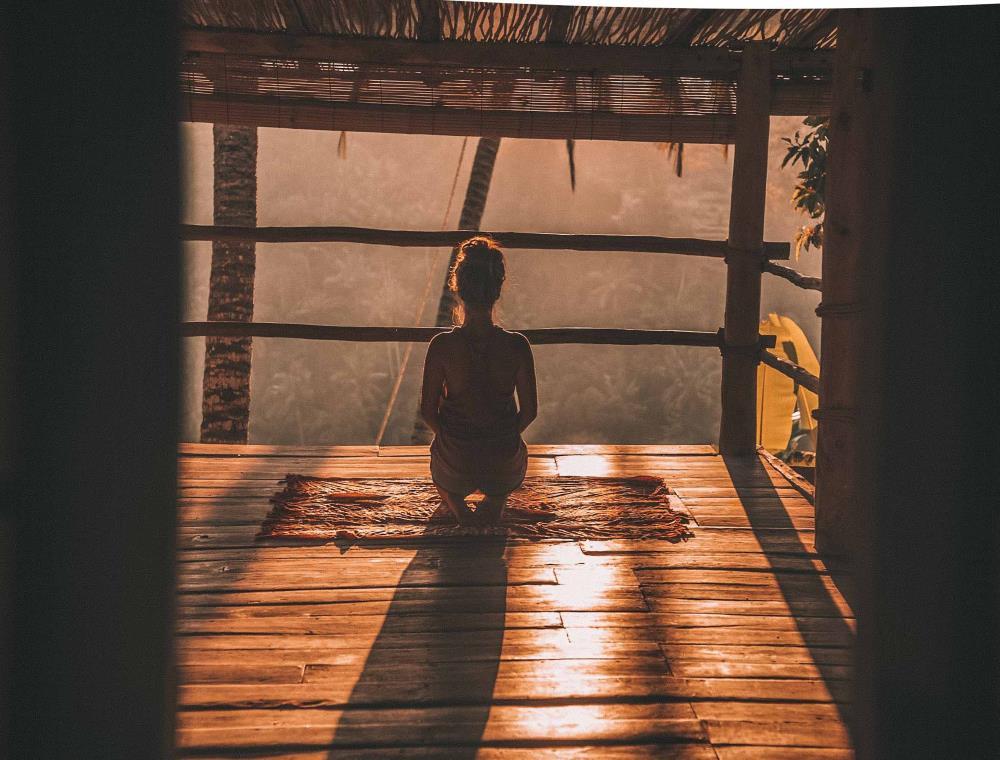 Женщина на веранде во время медитации в позе важдрасана