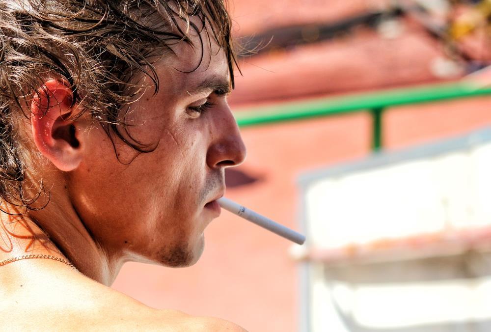 Мужчина в профиль с незажжённой сигаретой во рту