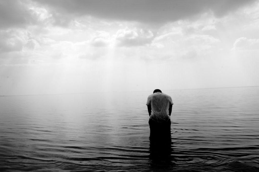 Человек с опущенной головой, стоящий по пояс в сером океане