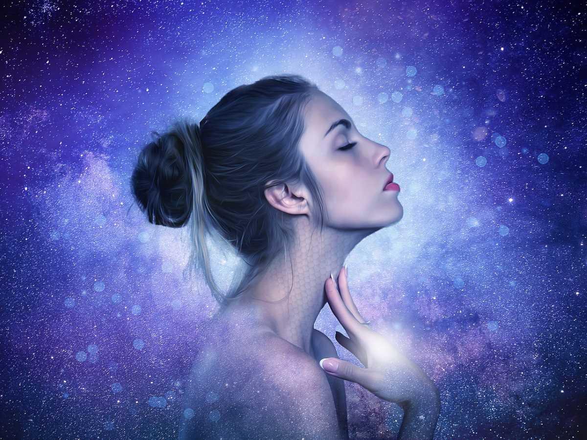 Красивая девушка с закрытыми глазами среди искрящейся энергии, с чувством прикасающаяся к шее