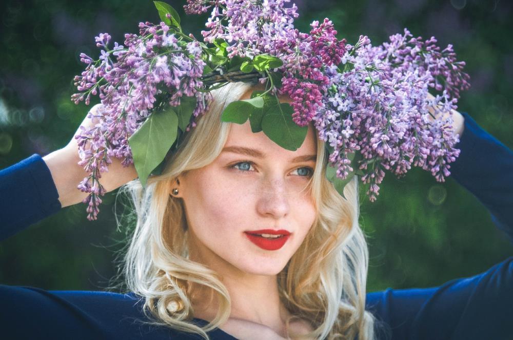 Красивая девушка весной с венком из сирени на голове