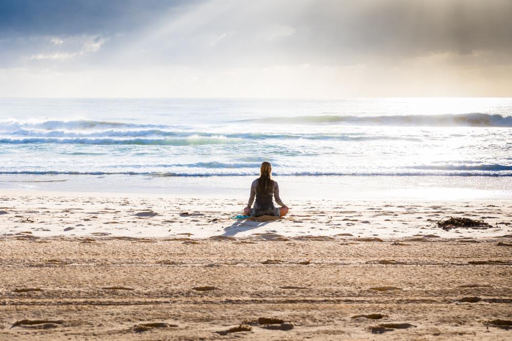 Женщина в процессе медитации на берегу океана