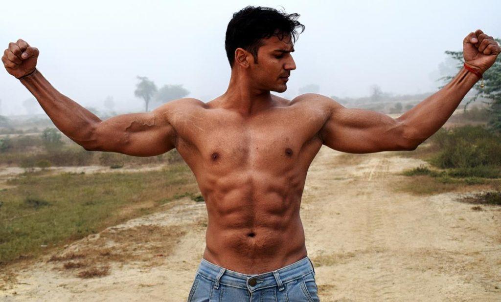 Загорелый мужчина с напряжёнными мышцами