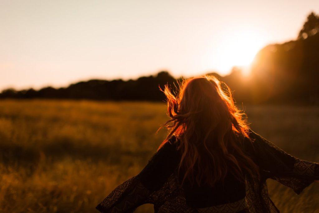 Девушка с длинными волосами, раскрывшая объятия рассвету
