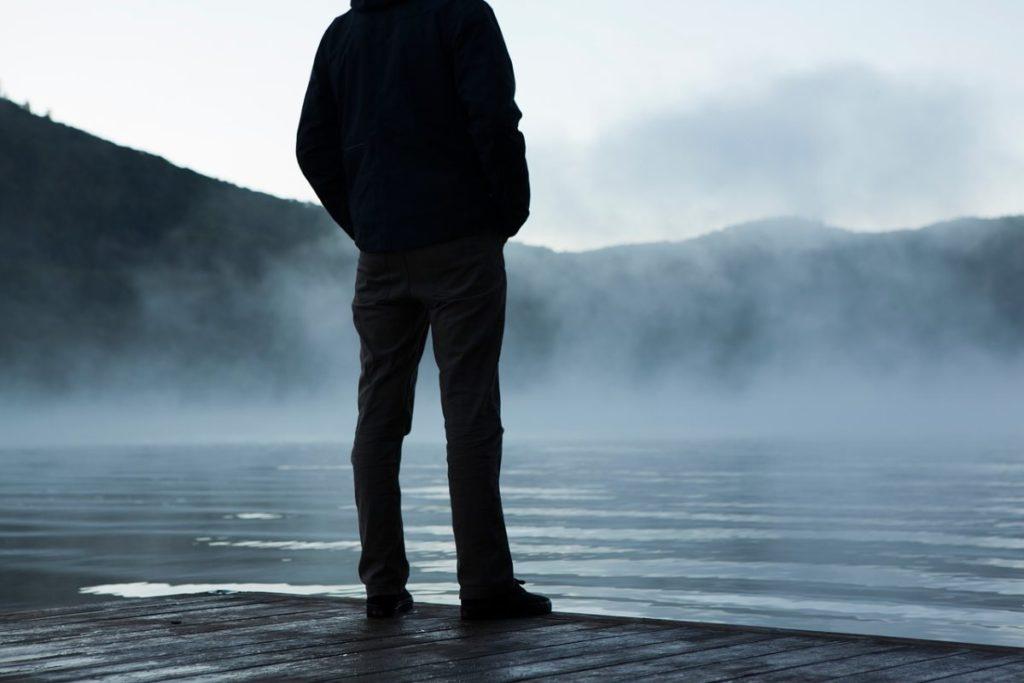Тёмный силуэт мужчины, который стоит один у кромки воды