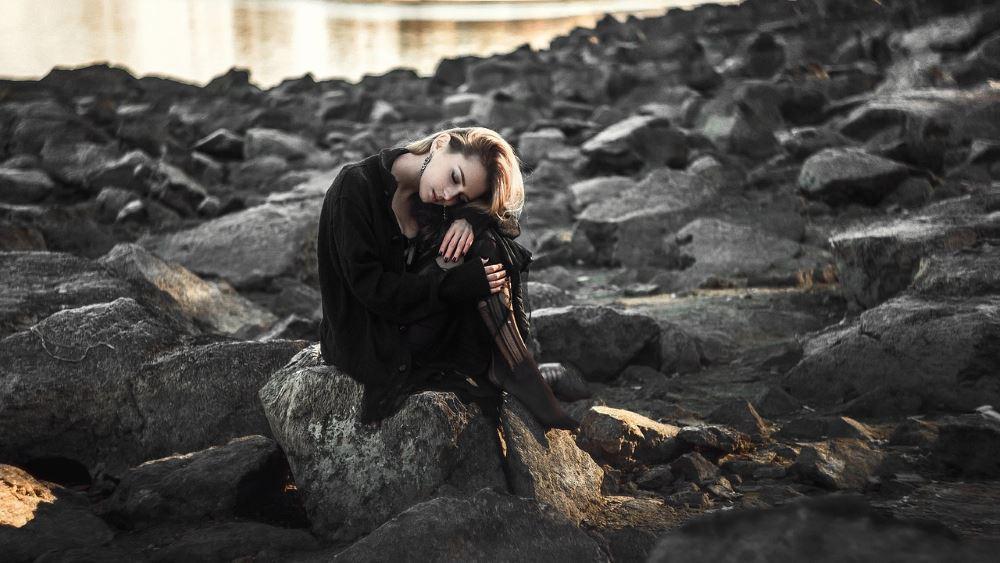 Одинокая девушка сидит на камне, склонив голову на колени