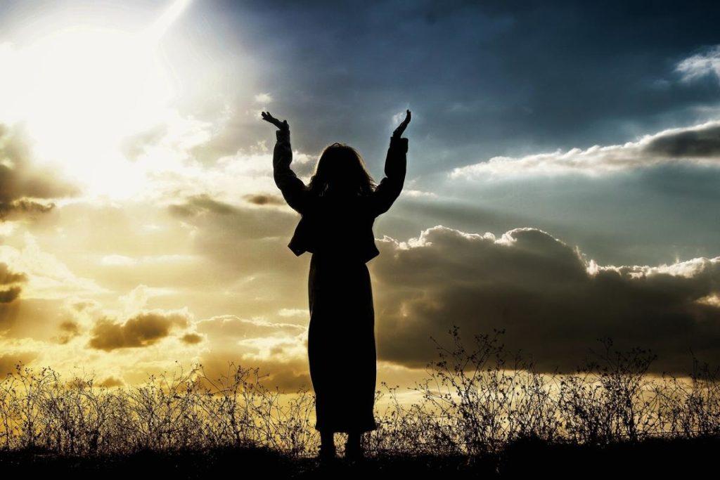 Силуэт женщины с руками, протянутыми в небо