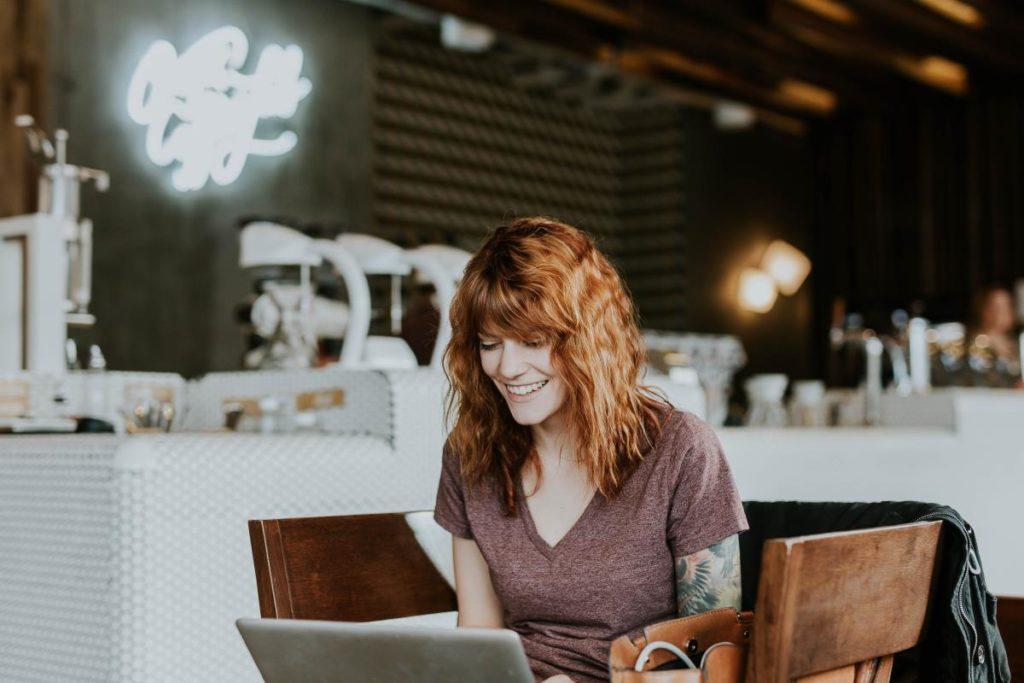 Женщина с рыжими волосами и татуировкой на руке улыбается, занимаясь делом за ноутбуком