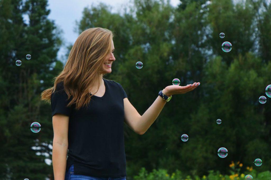 Девушка в окружении мыльных пузырей с чувством радости на лице