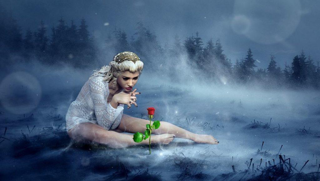 Красивая женщина в белом платье, визуализирующая розу посреди зимы
