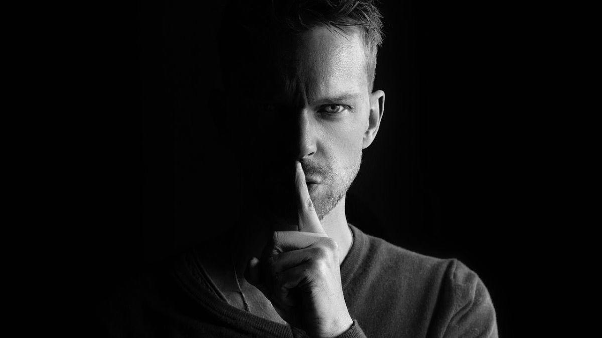 Мужчина, жестом призывающий хранить тайну