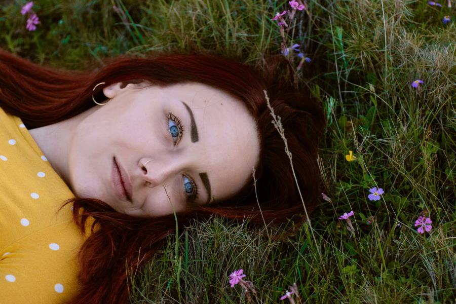Лицо красивой девушки, лежащей на земле, улыбаясь