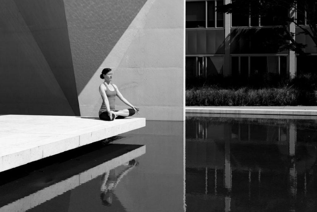 Женщина медитирует у воды, сидя на бетонном выступе