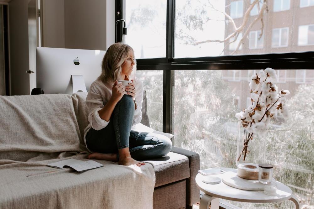 Женщина спокойно наблюдает за происходящим снаружи, сидя у окна
