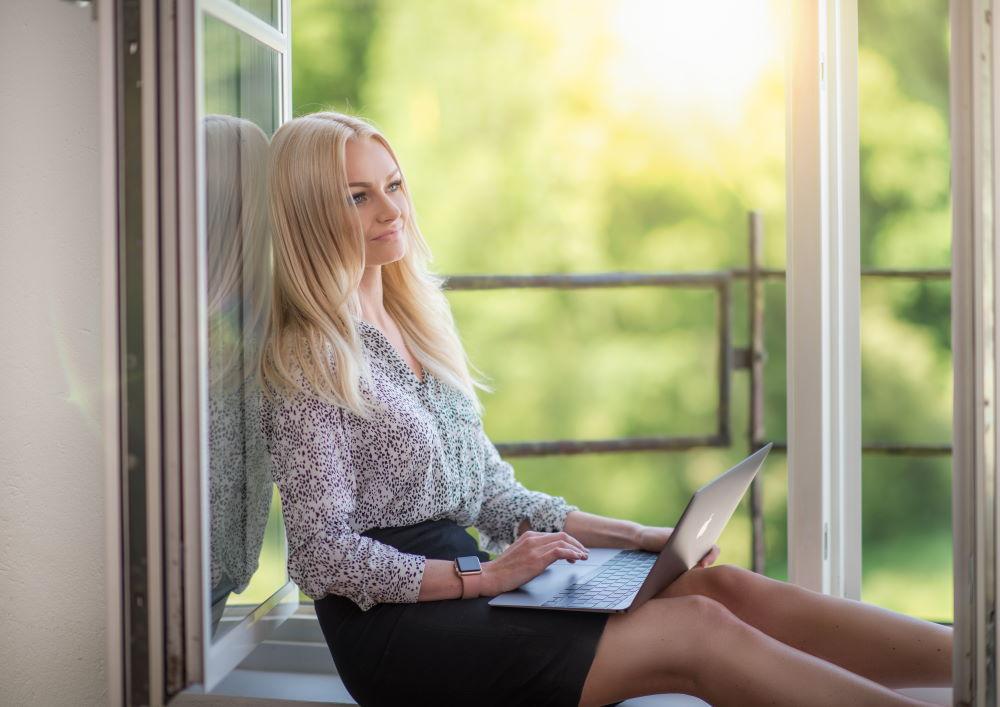 Сидящая у открытого окна женщина