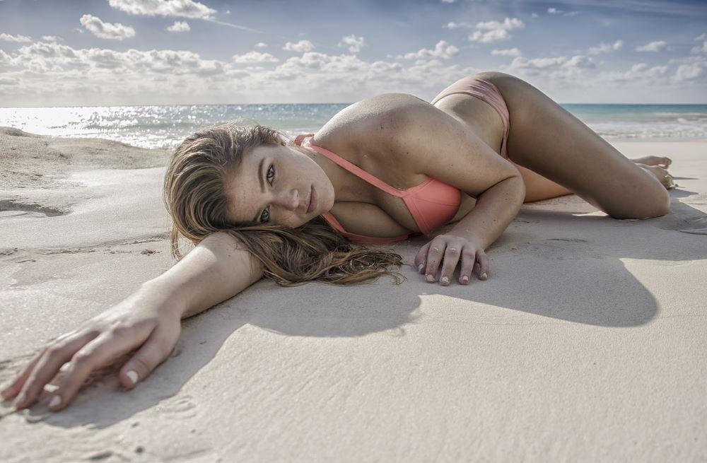 Красивая девушка, расслабленно лежащая на пляже