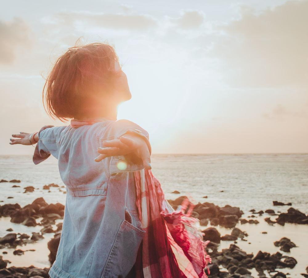 Девушка в состоянии достижения, расправившая руки на фоне сияния Солнца