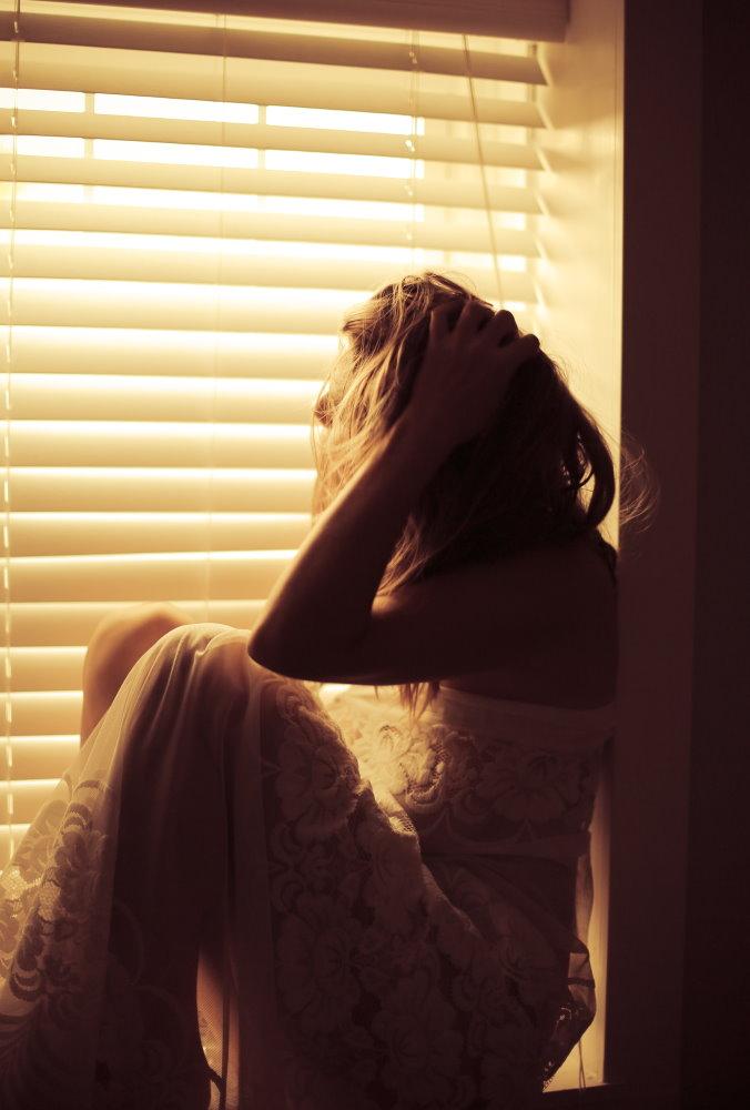 Женщина, сидящая на подоконнике у занавешенного окна