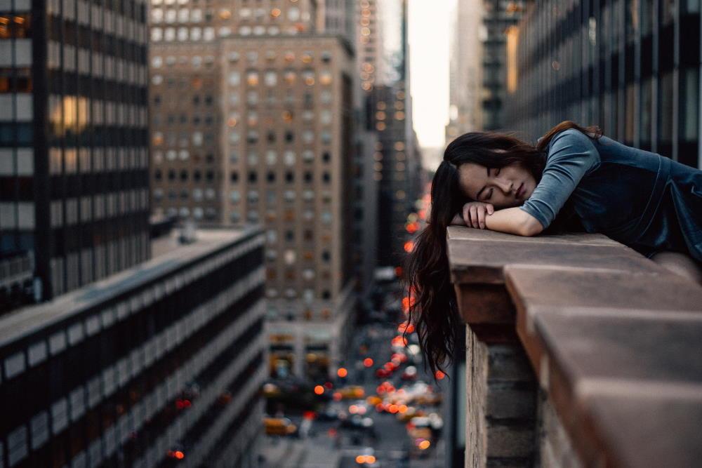 Девушка, истощённая напряжением, на фоне городского пейзажа