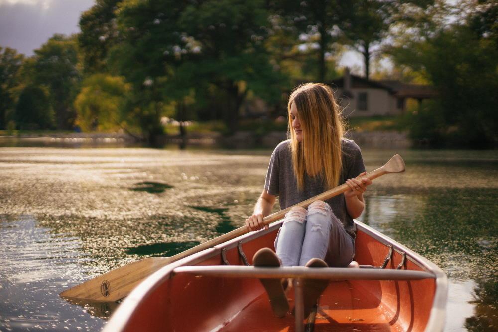 Девушка в лодке лениво работает веслом