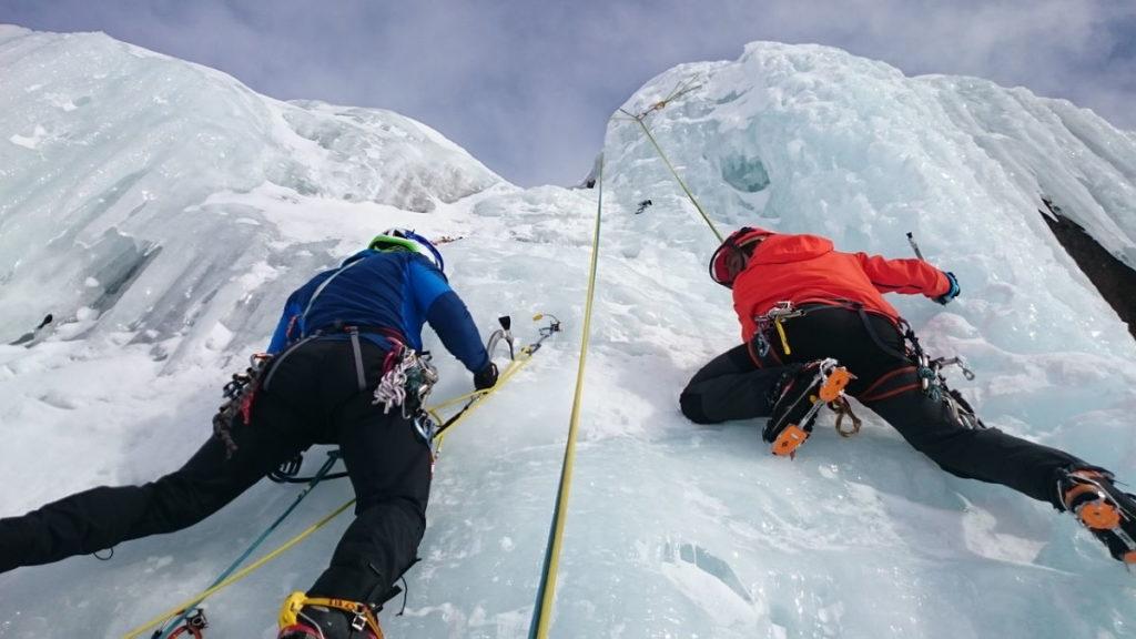 Двое мужчин, преодолевающих трудности подъёма на обледеневшую вершину
