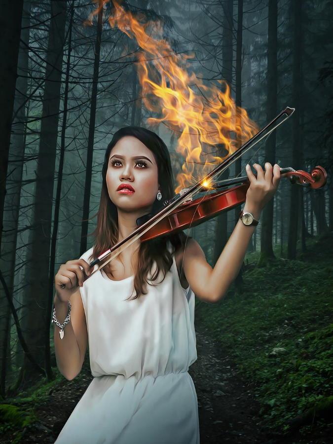Девушка, чьё лицо выражает страдание, а смычок, которым она играет на скрипке, объят огнём