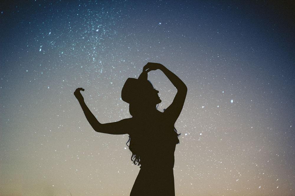 Силуэт девушки в творческом порыве на фоне звёздного неба