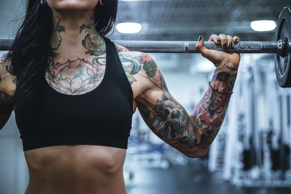 Торс женщины, занимающейся физическими упражнениями со штангой