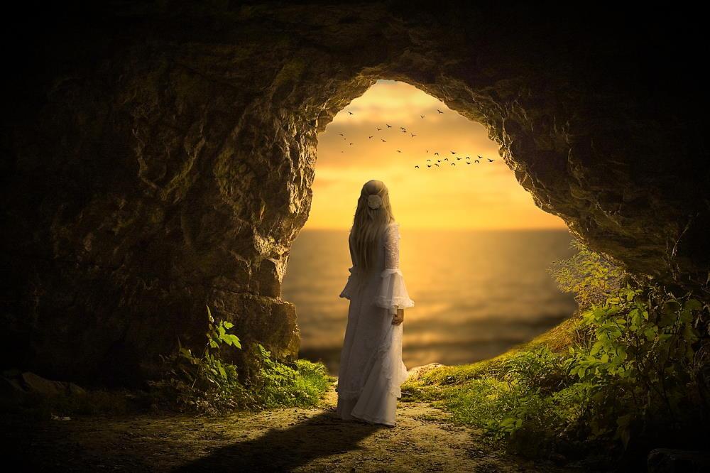 Женщина в белом платье, выглядывающая из пещеры