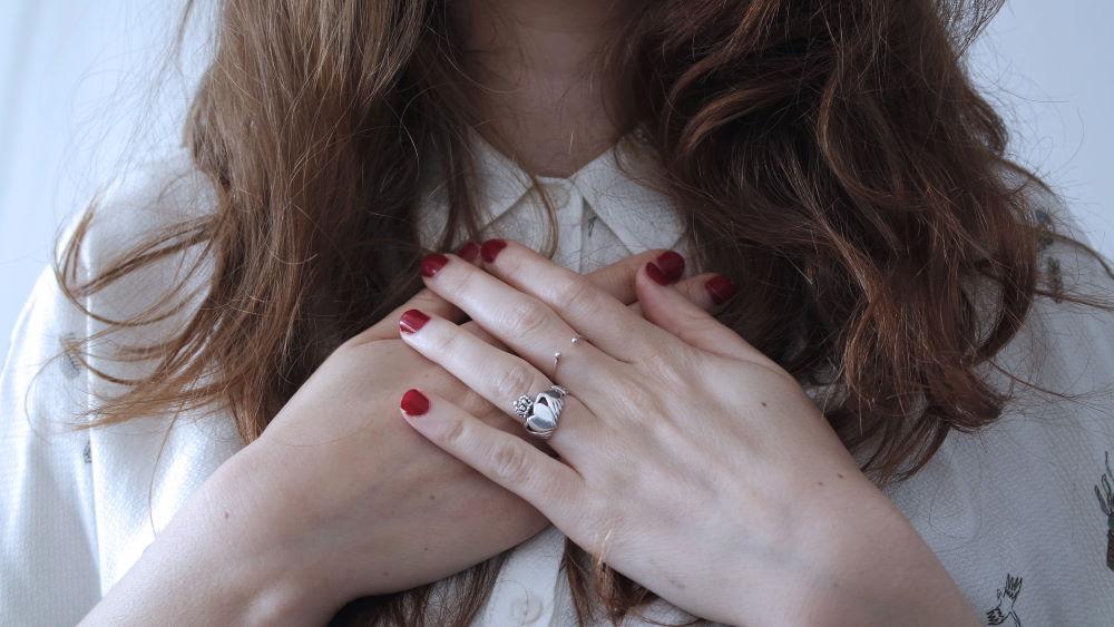 Женские руки, сложенные в жесте благодарности на области сердца