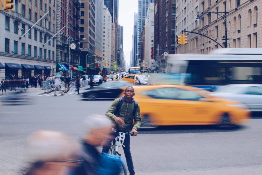 Мальчик на велосипеде посреди быстро движущихся людей и транспорта