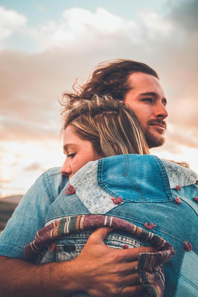 Мужчина, чей взгляд выражает готовность справляться с трудностями, обнимает женщину