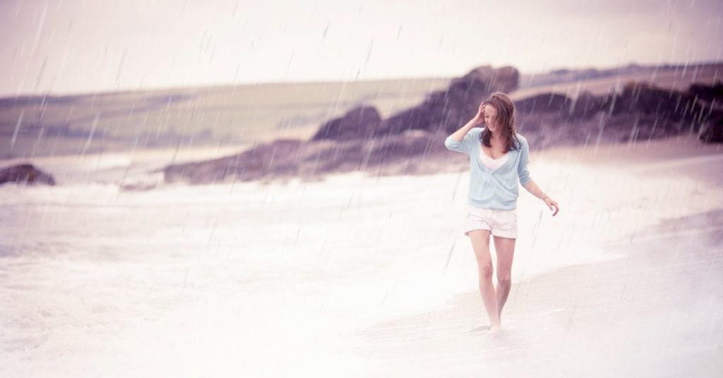 Девушка наслаждается жизнью, гуляя по берегу под дождём
