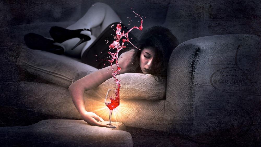 Женщина, упавшая без сил на диван, с бокалом вина в руке