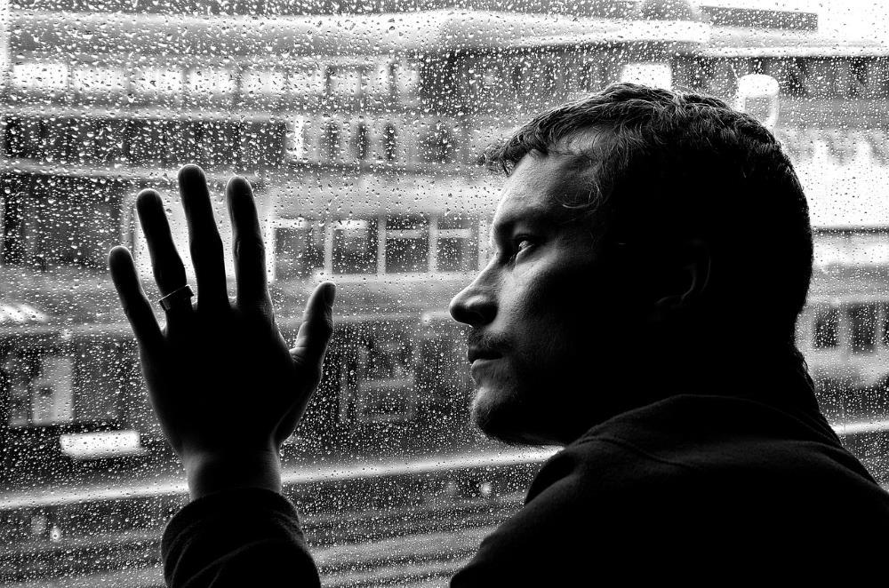 Одинокий мужчина у окна, окроплённого дождём