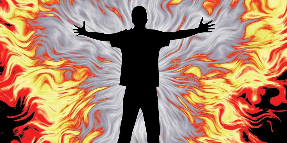 Силуэт мужчины с раскрытыми руками, готового принять огонь страдания