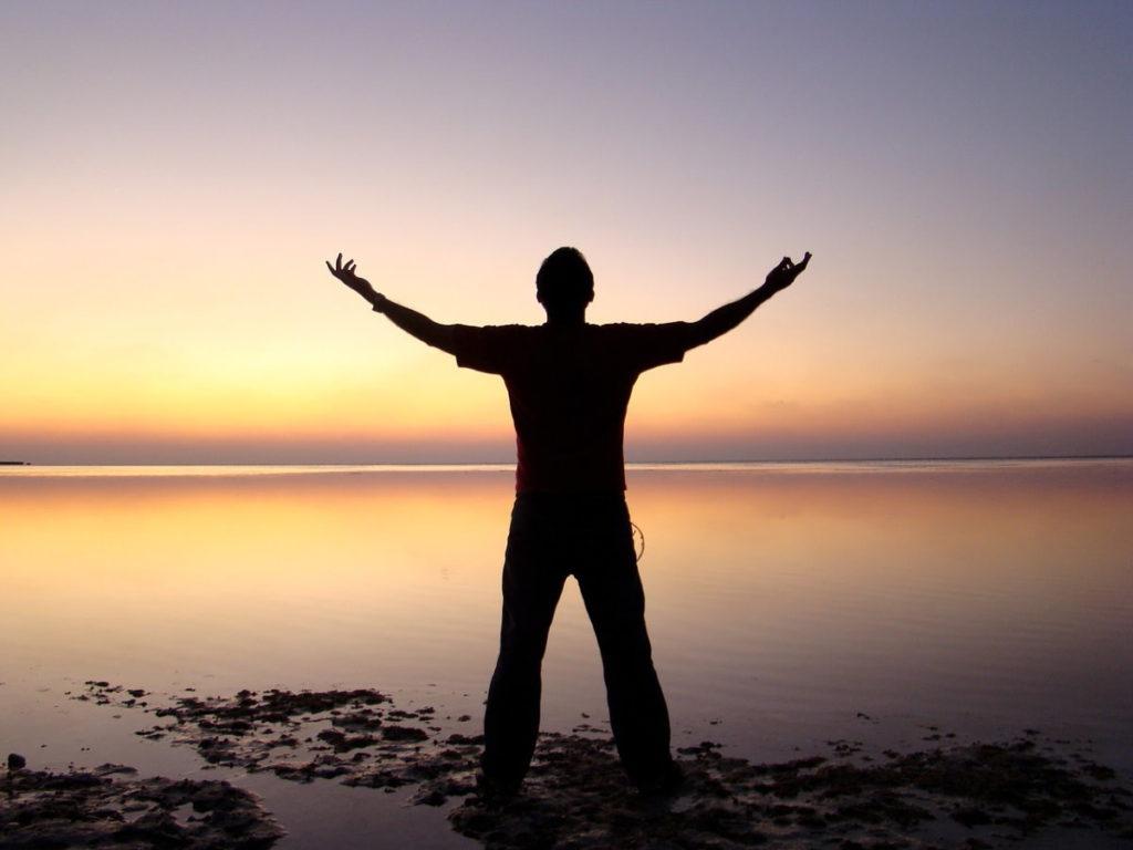 Мужчина с распростёртыми руками на фоне утренней зари