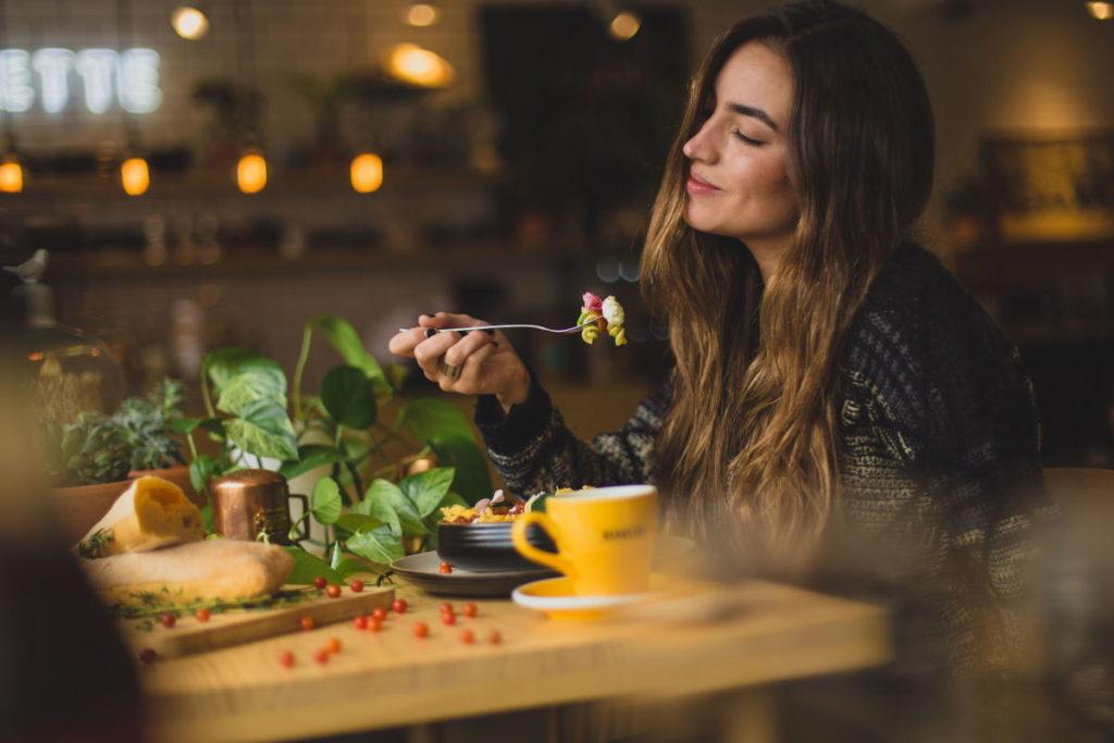 Красивая женщина, наслаждающаяся едой