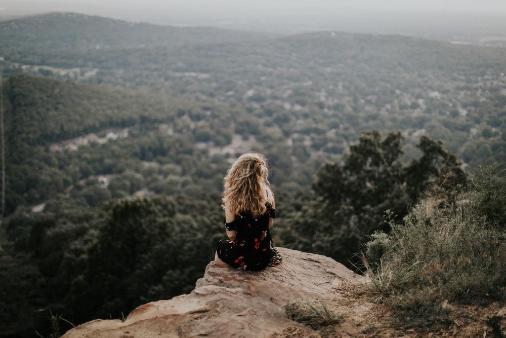 Женщина, сидящая в одиночестве на уступе скалы