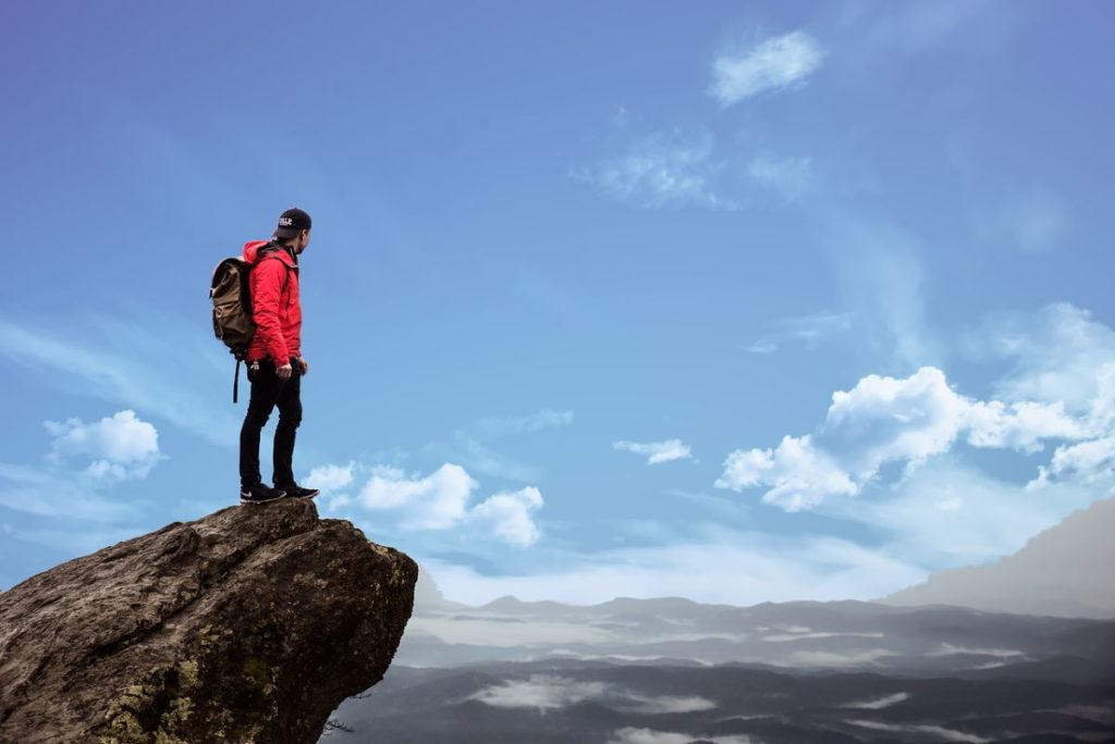 Мужчина, одержавший победу, забравшись на вершину скалы