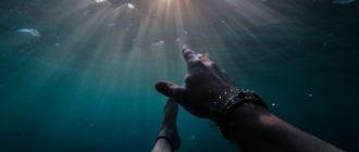 Мужская рука под водой тянется ко свету