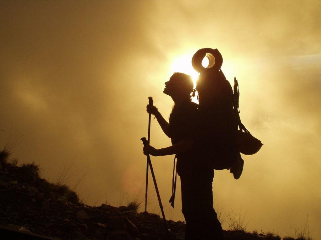 Человек, преодолевающий трудности подъёма в гору