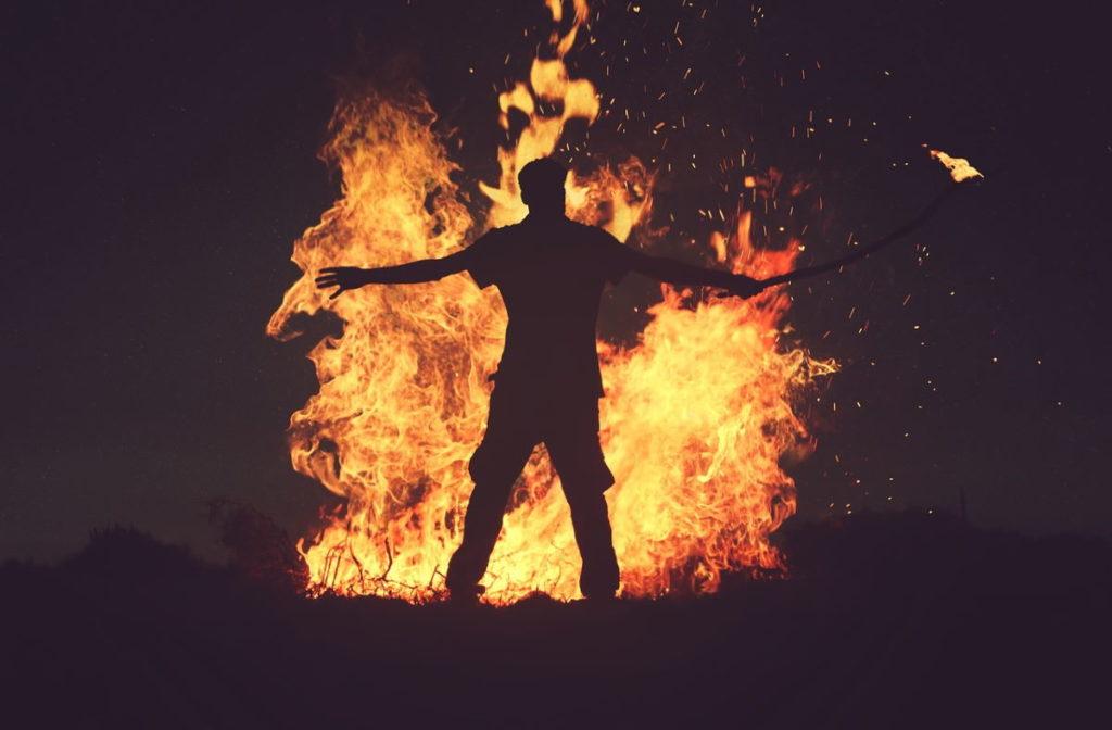 Силуэт мужчины у полыхающего огня