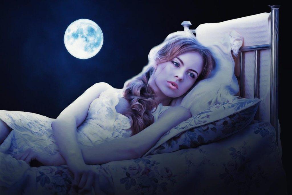 Женщина лежит в кровати, изнывая от скуки