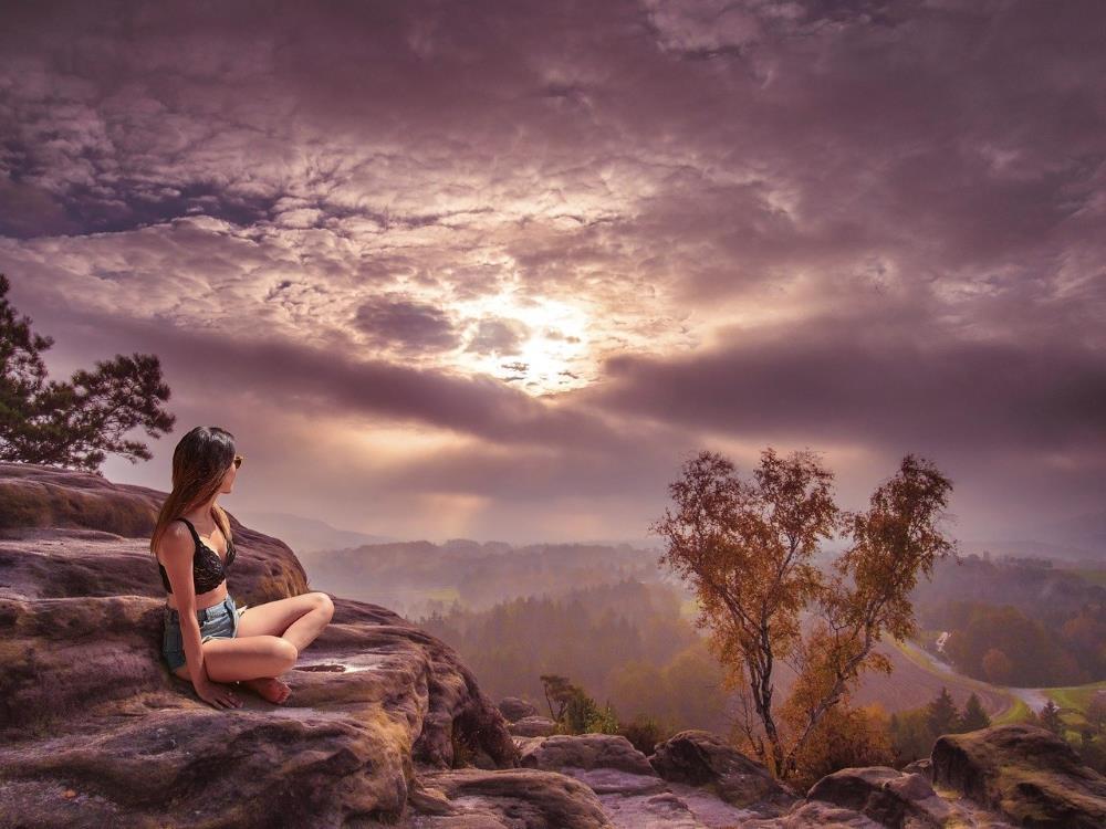 Девушка готовится к медитации, глядя на Солнце