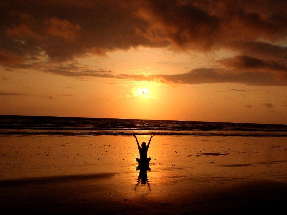 Силуэт женщины во время духовной практики на берегу океана